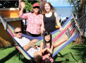 photo of 2 adults, 2 kids, outside by hammock